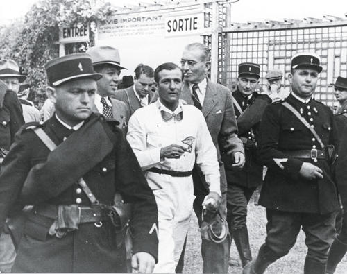 H.P. Müller 1939: Der Auto Union Rennwagenfahrer wird nach seinem Sieg beim Großen Preis von Frankreich zur Siegerehrung geführt. Links hinter Müller der damalige Auto Union Rennleiter, Dr. Karl Feuereiszen