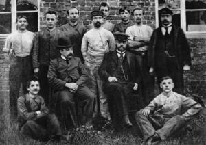 August Horch (mit Schirmmütze sitzend) und die erste Belegschaft seiner Motorwagenfabrik in Köln